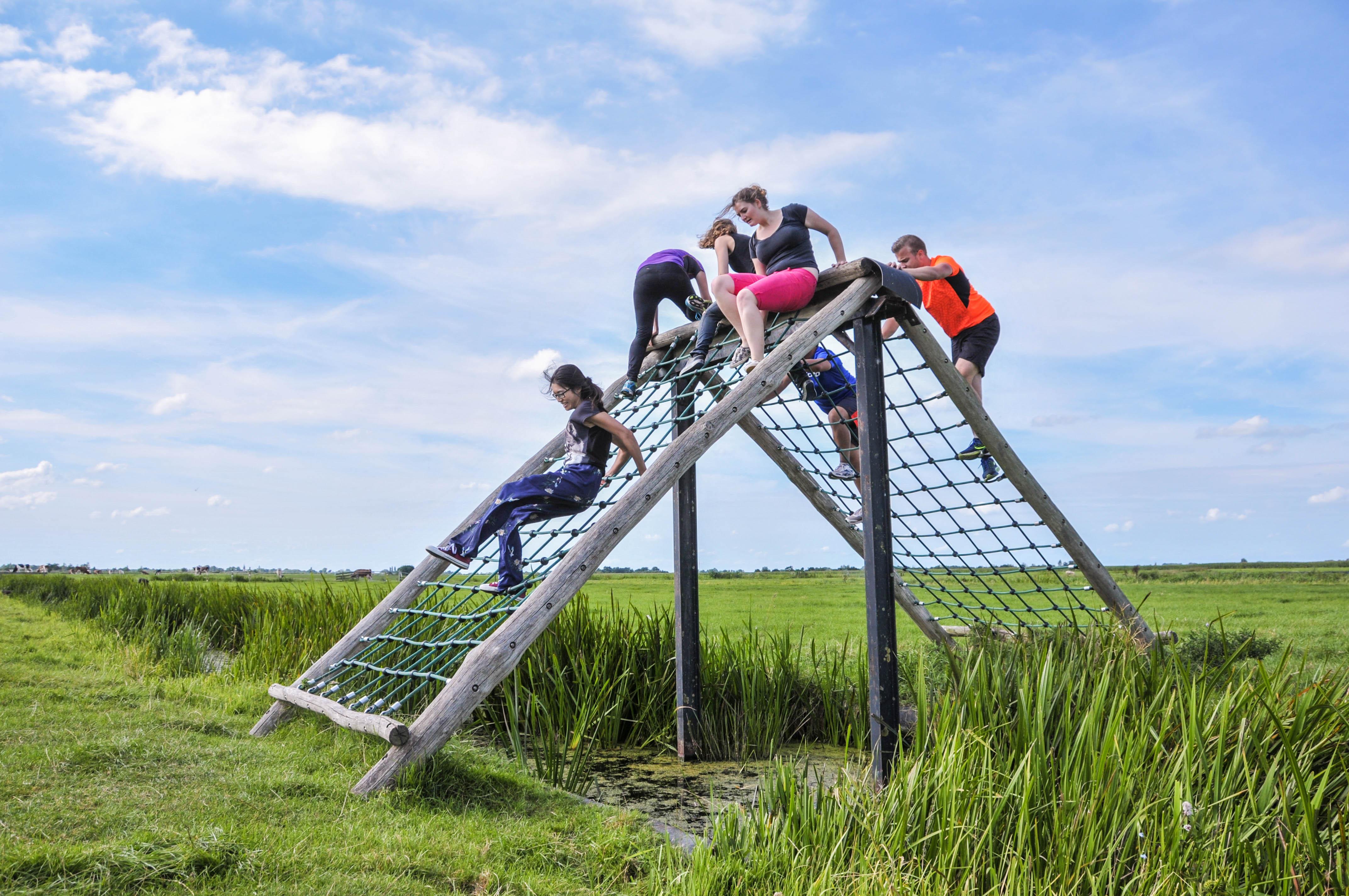 Groepje mensen probeert over de schuine brug te klimmen