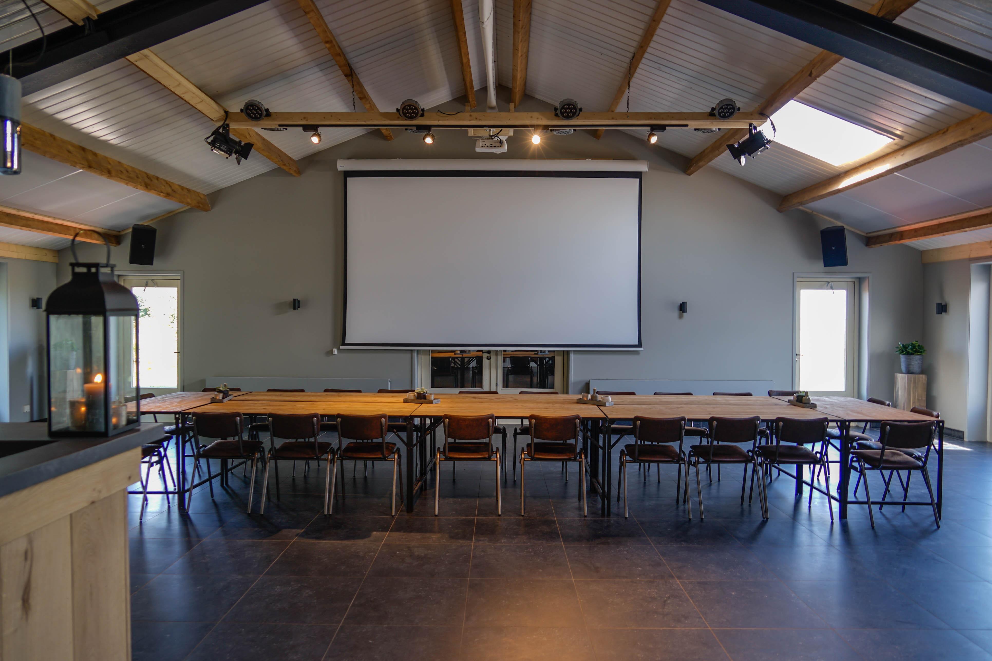 Vergaderruimte het Grechthuis met een groot beamerscherm en zicht naar buiten